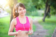 Running woman in park. Asian sport fitness model in sporty running clothes Royalty Free Stock Images