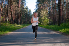 The running woman on path in forest in a sunny day Royalty Free Stock Photo