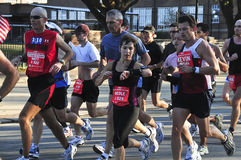 Running woman. Picture of a strong woman running the marathon with the men Stock Photo