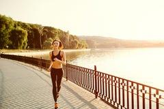 Running woman. Runner jogging in sunny bright light. Female fitness model training outside in park Stock Images