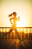 Running woman. Runner is jogging in sunny bright light on sunris Stock Images