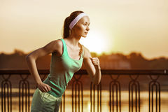 Running woman. Runner is jogging on sunrise. Female fitness mode royalty free stock photography