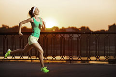Running woman. Runner is jogging on sunrise. Female fitness mode Royalty Free Stock Image