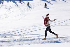 Running woman runner in winter mountains on snow. Royalty Free Stock Image