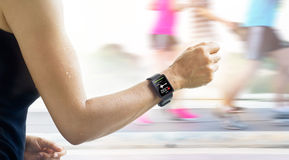 Running woman with smartwatch that show heart rate on the screen Royalty Free Stock Photography