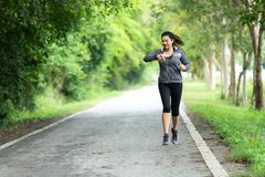Running woman. Sport Women jogging during and check timing. Outdoor Workout in a Park. Weight Loss and Healthy Concept stock photo