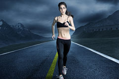 Running Woman. Sporty Woman runs on an empty Road Royalty Free Stock Image