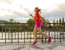 Running woman during sunny day in the city. Royalty Free Stock Photography