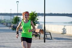 Running woman on the waterfront. Morning jogging. The athlete trains stock photos