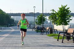 Running woman on the waterfront. Morning jogging. The athlete trains stock images