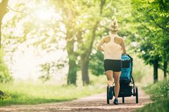 Free Running Woman With Baby Stroller Enjoying Summer In Park Stock Photography - 116833332