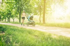 Free Running Woman With Baby Stroller Enjoying Summer In Park Stock Image - 116833361
