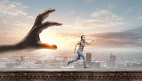 Running woman. Young woman in casual escaping from big male hand Stock Photos