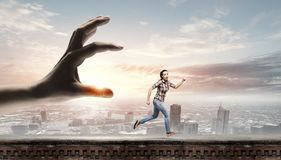 Running woman. Young woman in casual escaping from big male hand Royalty Free Stock Photos