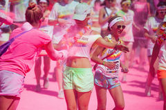 Running women at a color run in Cologne. Running women at a color run event in Cologne, Germany, covered with pink color powder Royalty Free Stock Photos