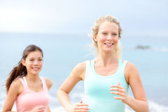 Running women - female runners on beach. Two women running partners jogging training outside on beach. Blonde women in focus Royalty Free Stock Photos