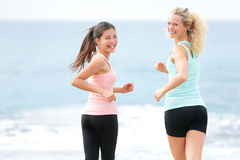 Running women jogging training on beach. Girlfriends runners exercising together smiling happy looking at camera. Two beautiful young women in workout Royalty Free Stock Image