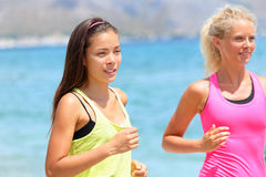 Running women runners training outdoors. Close up portrait of happy women runner jogging outside with friends on beach Royalty Free Stock Image