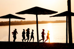 Running women silhouettes. On a beach at sunset Royalty Free Stock Images