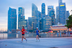 Running women, Singapore. SINGAPORE - MAY 06, 2012: Unidentified people runnig in front of Singapore downtown in Singapore. Singapore has been recognized as one Royalty Free Stock Photography