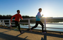 Running women. Two women running together along the bridge at sunrise Stock Photo
