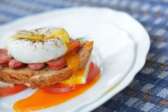 Running yolk of poached egg on sandwich with sausage, bread, cheese, tomato on white plate closely Royalty Free Stock Photography