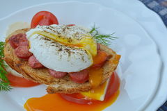 Running yolk of poached egg on sandwich with sausage, cheese, tomato close up. Orange running yolk of poached egg on sandwich with sausage, cheese, tomato on Royalty Free Stock Images