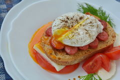 Running yolk of poached egg on tasty sandwich closely. Running yolk of poached egg on tasty sandwich with sausage, cheese, tomato, bread, pepper, salt on plate Royalty Free Stock Image