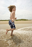 Running from you. Young boy running and smiling at the beach Royalty Free Stock Image