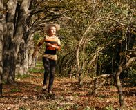 A running young blond hair woman, doing her athletic activity in the park. royalty free stock photography