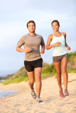 Running young couple jogging in beach sand happy. Running young mixed race couple jogging outside on beach happy smiling in summer sunset. Caucasian handsome Royalty Free Stock Photography
