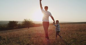 Running young dad with his three years old son, at sunset , amazing view. stock video footage