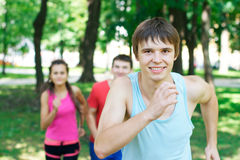 Running young happy man. Running young happy men with a couple jogging at the background Stock Photos