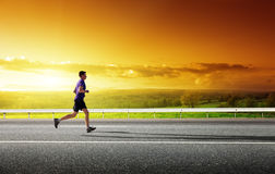 Running young man. Sunset and running young man Stock Images