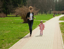 Running young mother and her daughter Stock Photo