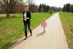 Running young mother and her daughter Royalty Free Stock Photos