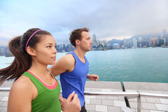 Running young people jogging in Hong Kong city. Running couple jogging in Hong Kong city. Runners training on Tsim Sha Tsui Promenade and Avenue of Stars in Royalty Free Stock Images