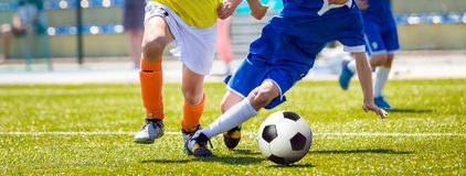 Running Young Soccer Football Players. Youth Soccer Competition Between Two Footballers. Football Stadium in the Background royalty free stock photo