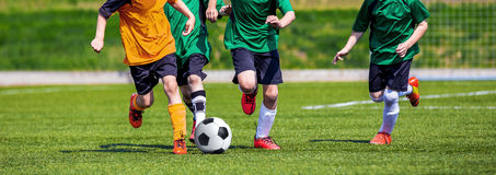 Running Youth Football Players. Kids Playing Football Soccer Game Royalty Free Stock Photography