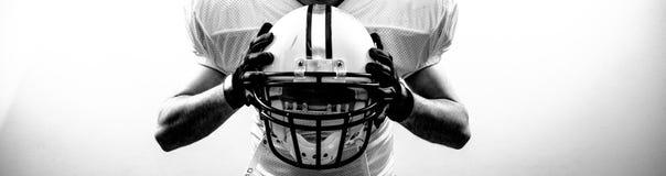 Runningbackquarterbacken för amerikansk fotboll tar en hjälm