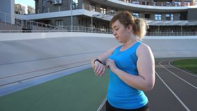 Runnner de la mujer que elige opciones en la pulsera de la aptitud metrajes