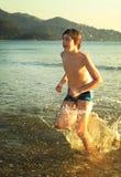 Runnung adolescente del muchacho en el mar en la sonrisa del fondo de la playa de la montaña Fotos de archivo libres de regalías