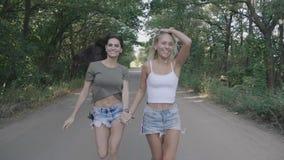 Runnung för två flickor för bästa vän parkerar sexig varm och hagyckel tillsammans på en väg på skogen eller stock video
