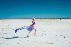 Runnung kvinna i den violetta klänningen Arkivfoto
