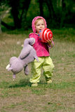 Runnung toddler with a ball. Runnung little girl with a ball and a hippopotamus royalty free stock photo
