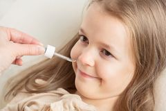 Runny nose in children. Mom is dripping in the nose girl drops royalty free stock images