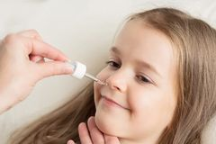Runny nose in children. Mom is dripping in the nose girl drops stock photo