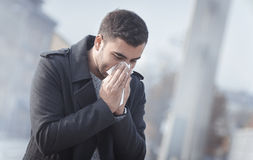 Runny nose. Man blowing his nose on street. Outdoors Stock Images