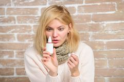 Runny nose and other symptoms of cold. Nasal spray runny nose remedy. Girl sick person hold nasal drops and tissue. Allergy concept. Home treatment. Nasal stock images
