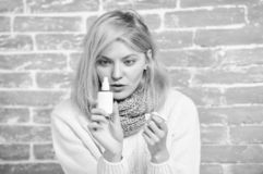 Runny nose and other symptoms of cold. Nasal spray runny nose remedy. Girl sick person hold nasal drops and tissue. Allergy concept. Home treatment. Nasal stock image